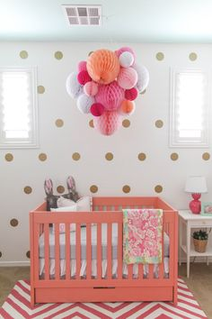 The most unexpected thing in this coral and gold nursery? A mint green ceiling - obsessed!