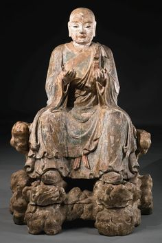 A RARE POLYCHROME WOOD AND GESSO FIGURE OF MAUDGALYAYANA, ONE OF BUDDHAS TWO CHIEF MALE DISCIPLES, SONG / YUAN DYNASTY