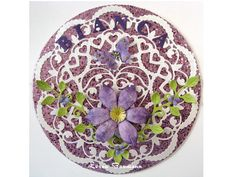 Circle shaped card cut with a Spellbinders grand die with purple glitter paper circle layered over it.  Doilyand leaf corner are from Cheery Lynn.  Flower is from Heartfelt Creations.