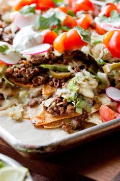NYT Cooking: Nachos are among the most ubiquitous of America's pastime foods. At ballgames, carnivals or bowling alleys you can expect a pile of limp tortilla chips, drowned in warm yellow cheese product. But nachos should, and can, be better than this. Try them showered in good shredded cheese and accompanied by a fragrant meat sauce, the fire of jalapeños, the chill and silkiness of sour cream, the tart e...