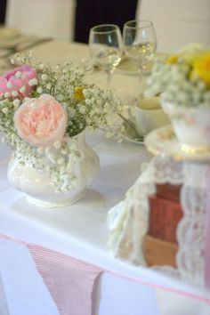 Vintage style summer Tea Party Tea cups wedding style table decor Pastel blooms and old vintage books covered in lace and ribbon contact www.blushrose.co.uk Manchester wedding flowers