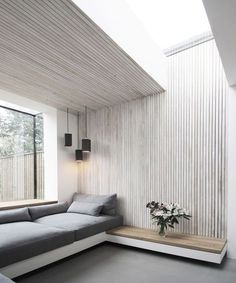 Spacious grey living room: Wooden walls, great roof and side windows and black corner lighting.