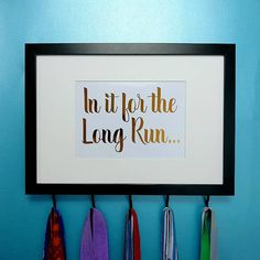 "Medal Holder Frame In It For The Long Run Funny Quote Foil Print - Essential for all those with medals to be proud of! Great for long distance runners, marathon runners or those that are dedicated to the cause! Whether its for 1 medal or many, show how proud you are of your achievements and show them off with this beautiful medal display. Foil quote reads ""In It For The Long Run"""