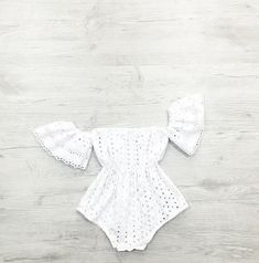A beautiful broderie anglaise fabric fully lined white 100% cotton. Featuring off the shoulder style. Perfectly shaped waist with stretchy elastic. This beautiful romper is just perfect for those summer beach days.