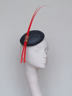 A hand blocked navy sinamay button fascinator. Very chic with orange/red quills…
