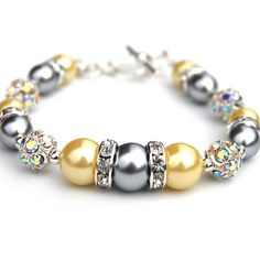 Silver grey and lemon pearls combine with shimmering rhinestones to make this a lovely gift or bridesmaid accessory.  I have strung 8mm glass pearls with 8mm rhinestone fireballs and rondelles.  The bracelet measures 7.5/19cm and is finished with a silver plate toggle clasp. If you need the length of the bracelet adjusted, just leave a note of the desired length in the message to seller.  Like this bracelet but prefer a different colour? Check out my other bling pearl bracelets here - ht...