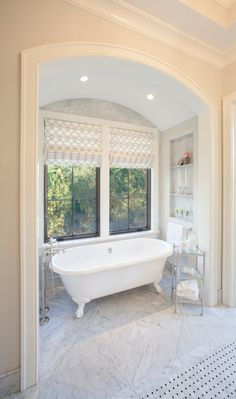 Arched bathroom alcove features clawfoot bathtub paired with floor-mounted tub filler and glass top etagere flanked by marble tiled niches and situated under windows dressed in white and gray geometric roman shades atop marble tiled floor.