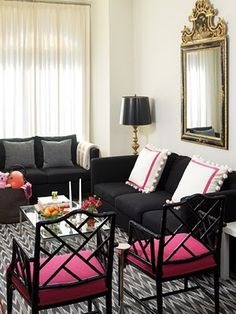 I really like the white pillows on the black couch, and the unique chairs with colored cushions.