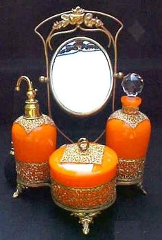 A Czechoslovakian Orange Glass Dresser Set 4 Pieces   the holder with morror, tqo perfume bottles and a powder box, circa 1918-1939