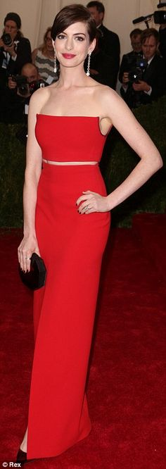 Best dressed @ 2014 Met Gala | Anne Hathaway in a red Calvin Klein strapless crop top & skirt ensemble paired with a burgundy box clutch an matching pumps
