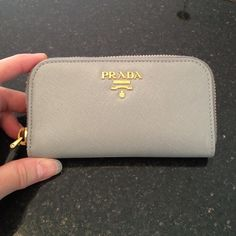 Prada Key Holder. Authentic. Saffiano grey leather. Gold Prada logo on front. Zipper closure. 6 hooks for keys. 2 inside slit pockets. Gold plated hardware. Some small markings on the metal bar inside as shown in pic four. Otherwise it's in great condition. Prada Accessories Key & Card Holders