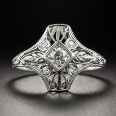 From the 1920s-30s, an Art Deco delight that works beautifully as a modestly proportioned dinner ring or as a distinctive vintage engagement ring. Die-struck and hand-finished in platinum, a quarter-carat European-cut diamond center stone radiates in all directions with four tiny single-cut diamonds and a pierced foliate or wheat motif. A hand-engraved upper ring shank adds the finishing touch to this consummate Jazz Age jewel. Currently ring size 7 3/4.