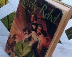Vintage Lovely Rebel Hardcover Book $14.00 | This is a Romantic novel by Muriel Marshall copyright 1950 and printed in the United States.  Published by  RInehart & Company publishers.  It is a hard cover with dust jacket and 305 pages.     It is in good vintage condition.  The dj has wear to it as shown in pictures as some dark coloring on ends/tips of pages also shown in pictures.