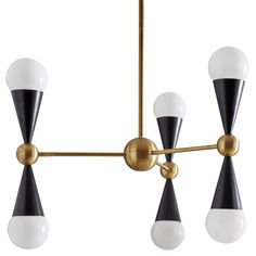 Kinetic Modernism.Simple geometric shapes—cones and spheres—collide with dynamic results. Antiqued and blackened brass create a chic and classi