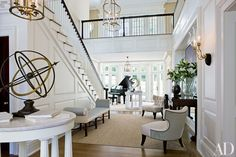 Designer Thomas Pheasant added a bay to brighten a Virginia home's entrance hall, where Luis Montoya and Leslie Ortiz's Two Plums is displayed with a pair of armillary spheres; Pheasant designed the chairs for Baker   archdigest.com
