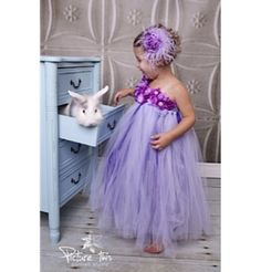 She'll look like a Grecian beauty in the gorgeous flowering layers of the lavender one- shoulder tutu dress. This elegant gown adorned with pearled buttermilk blossoms is designed to fit girls up to size 12 (size may vary).