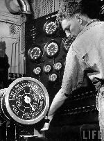 Navy engineer manning ships throttle next to steam gauges in the battle station of the battleship Maryland, 1939. Photographer: Margaret Bourke-White.
