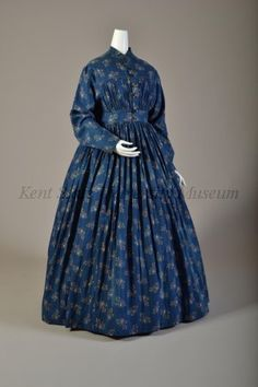 "Indigo dyed cotton w/ yellow printed leaf & stem pattern & white resist leaf veins; mandarin collar, bodice gathered from F & B yoke to wide waistband, CF opening w/ hand buttonholes, side pan- els, L shaped sleeves, very full gathered ankle length skirt; bodiced lined in natural linen; CB 55.5"" Kent State Univ Museum"
