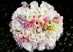 Bridal bouquet of roses, dahlia, ranunculus, lisianthus, and sweet peas