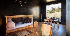 Per il living del suo capanno di multistrato dipinto di nero Michael Lett sceglie un daybed in legno di Donald Judd, sedie e puf artigianali. Lo sgabello vintage è di Alvar Aalto, Artek. A sofftto una bacchetta mobile, opera dell'artista Eleanor Cooper