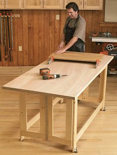 """Folding Work Table Woodworking Plan The 1x4 base construction, topped with a hollow-core door, make it easy to single-handedly make room in the garage for the family car. Or, for use as an outfeed table, simply build it 1/8"""" less than the height of your tablesaw."""
