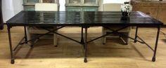 Unieke industriele tafel met zwart gelakt blad en ruig metalen onderstel voorzien van wieltjes.