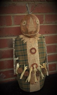 """This Pumpkin scarecrow is all made of cotton. His body is green homespun that has been over dyed for a more primitive look. His head is painted and sanded and his face is all hand stitched. He has 3 handmade felt buttons. His twig arms hold a garland made of dried corncobs and husks. He is 20"""" tall and is free standing. This guy would make a great center piece to any Fall decor.    All my offerings are hand made by me right here in the mountains of NC. I use antique fabric as much as I can…"""