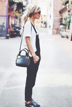 A white t-shirt is layered under black overalls and worn with a black shoulder bag, Nike sneakers, and sunglasses