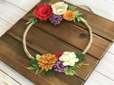 This listing is for a Felt Flower Wreath wall hanging. A medium stained wood plaque is the backdrop for this handmade wool felt wreath. Wreath is made from natural twine rope and flowers are hand cut from a wool felt blend fabric. Artificial flowers are added to create texture. This