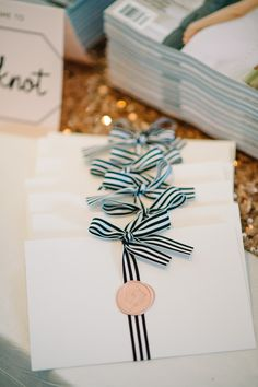 White programs tied with black and white striped ribbon and sealed with blush wax seal with South Carolina emblem. Event for The Knot. Planning and design by Mac & B. Events www.macandbevents.com // Programs by The Silver Starfish // Picture by Aaron & Jillian Photography