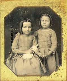 2 girls in matching dresses with papier-mache doll