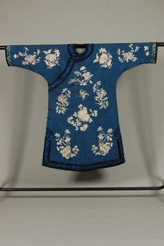 China lady's changfu (informal robe), Chinese, circa 1900, blue damask silk ground, worked in pastel silks with chrysanthemum, peonies, butterflies, with blue satin-stitched floral border