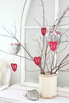 Create a Valentine's tree by stuffing several branches into a stone pot or vase.  (They could be spray-painted white, if desired.)  Decorate with heart ornaments.