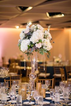 A chic tall white centerpiece with touches of pink and blush roses and hints of greenery make it the perfect choice for a spring wedding! #springwedding #springweddingideas