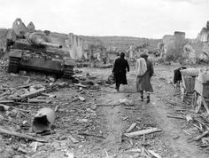 French refugees return to the ruined town Mitlevir in Feb 1945. On the left lies a disabled German tank destroyer Jagdpanzer IV 70(A).