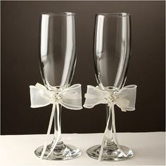 "Toasting Flutes - Fantasy - WeddingDepot.com - 252-K388 Add a special touch to your wedding reception and to your cake table with these toasting glasses.  Set includes two toasting glasses measuring approximately 8.5"".  Each flute is accented with a bow that you can incorporate into your wedding theme.  Bows are available in ivory."