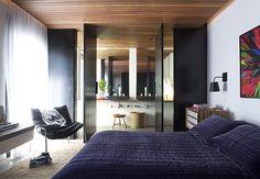 O teto revestido com ripas de cedro destaca-se no quarto, assim como as portas pivotantes pretas, que se abrem para o banheiro