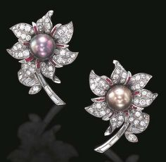 A PAIR OF PEARL, RUBY AND DIAMOND FLOWER EAR CLIPS  Each centering upon a brown pearl, measuring approximately 10.70 mm, to the circular-cut diamond petal surround, with calibré-cut ruby accents, extending circular and baguette-cut diamond stem and leaves, mounted in platinum