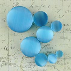 Blue Cat Eye: This beautiful blue stone is very smooth and the chetoyancy effect is light blue. Quantity: Sold as 1 pair (2 pieces) Style: round cut plug, 2 sides flat Flare: Double flare (saddle) Wid