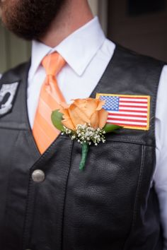 Harley Davidson boutonniere with an orange rose and baby's breath. The groom wore a white shirt, orange tie, and a black leather motorcycle vest complete with patches. Photo by nallayerstudios.com
