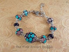 Hand Torched Chunky Lampwork Bead Bracelet Teal Purple and Black No. 38 by Outwestjewelry on Etsy https://www.etsy.com/listing/181551879/hand-torched-chunky-lampwork-bead
