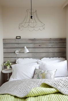 Gorgeous bedroom with reclaimed wooden slat headboard mounted with a white adjustable desk lamp.