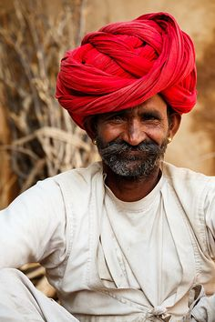 A portrait of a Bishnoi man wearing traditional clothing and a red turban, located in a small village called Dudiya near to the Blue City of Jodhpur.