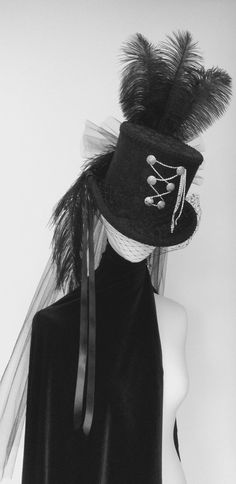 Black lace top hat featuring silver buttons and silver chain corset , black Satin ribbons, mid back bustle veil, merry widow face veil and crown and  side ostrich plumes.  A striking and dramatic hat.  Custom made in my own workshop in Ayrshire Scotland  https://www.etsy.com/uk/shop/Blackpin?ref=hdr_shop_menu   Shop this product here: spree.to/augr   Shop all of our products at http://spreesy.com/JewelsByScarlett      Pinterest selling powered by Spreesy.com