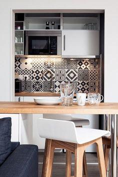 Кухня в нише нейтрально белая с деревянной столешницей. Кухонный фартук выполнен из черно-белой кафельной плитки со скандинавским узором.