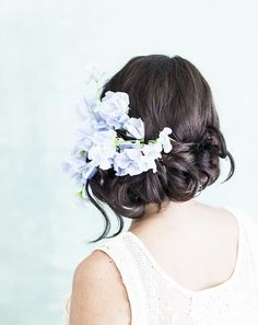 Accent a twisted hairdo with a sprig of sweet peas.