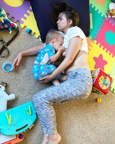 Toddler and mother sleep on floor as child breastfeeds