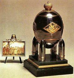 """Due lisce fasce orizzontali dividono il guscio in tre sezioni, quella centrale è decorata con placche d'oro traforate che raffigurano: San Giorgio che uccide il drago incorniciato da una losanga di foglie d'alloro; la data """"1916"""" in un circolo d'alloro; l'emblema russo, costituito da un'aquila bicipite sotto tre corone; il monogramma della zarina Aleksandra Fëdorovna, anch'esso in un circolo d'alloro."""