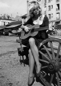 Brigitte Bardot playing the guitar in a classic solid/gingham dress. #modcloth #styleicon