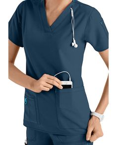 SOUND DESIGN    Get easy access to tunes and calls—and keep that cord wrangled up—with this smartly designed Cross-Flex women's scrub top from Carhartt. This top has a hidden cell phone pocket built right in, plus a unique cord loop sewn into the V-neckline. Other pocketing includes patch pockets, a divided instrument pocket and a double arm pocket that's perfect for pens and penlights. The comfy Cross-Flex fabric includes moisture-wicking and stain release technology.      Carhartt…
